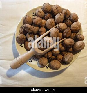 View from above on harvested walnuts and wooden chute in vintage ceramic bowl - Stock Photo