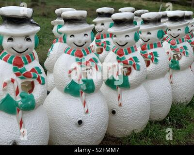 Two rows of plastic snowmen dressed is green and red earmuffs scarf and mittens - Stock Photo