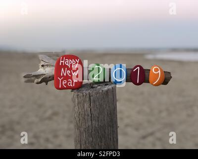Happy New Year 2019 with a colored stones composition on a wooden pole - Stock Photo