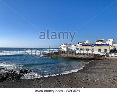 View of the black volcanic beach and small white buildings, ocean bay landscape, fishing village on the Atlantic coast of Fuerteventura - Stock Photo