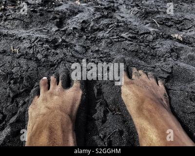 A pair of feet on top of black sand - Stock Photo
