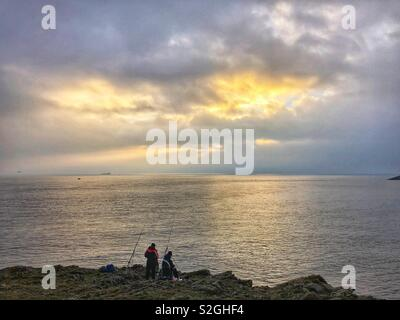 Two fishermen fishing off rocks at dusk in Barry, South Wales. - Stock Photo