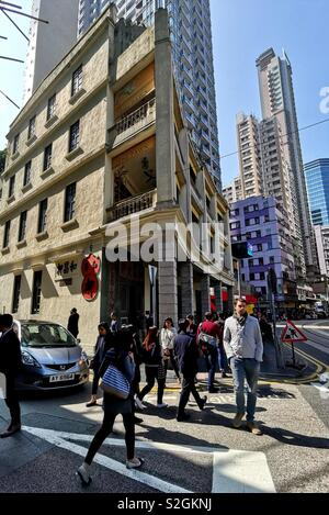 Crowed walking on Johnston street by a beautiful old building in Wan Chai, Hong Kong. - Stock Photo