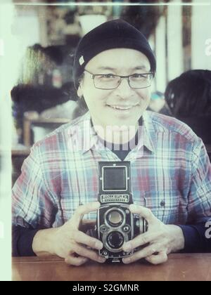 Happy middle aged Asian man holding vintage film Rolleiflex camera - Stock Photo