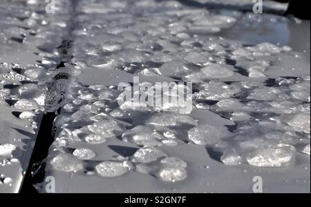 Melting ice globules on a clean white car - Stock Photo