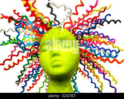 A lime green mannequin head with colorful sprains of hair protruding in all directions on a white background - Stock Photo