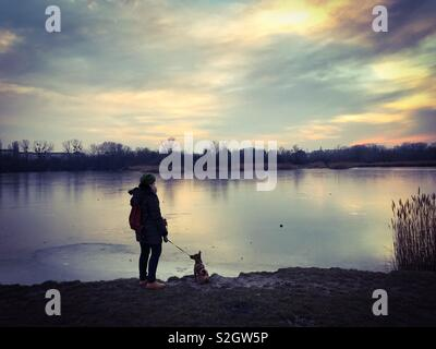 Woman and her dog standing near the lakeside of a frozen Lake - Stock Photo