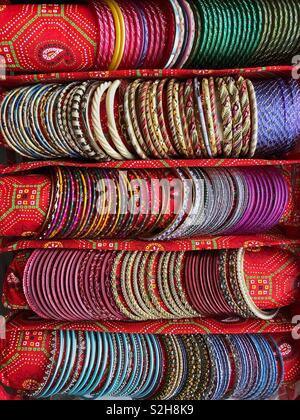 Rows of colourful Indian bangles on display in a specially made carry case. - Stock Photo