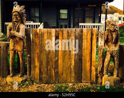 Carved wooden statue of sullen Indian chief with crossed arms and surly cowboy with hands in pockets stand on each side of wooden gate in front of house - Stock Photo