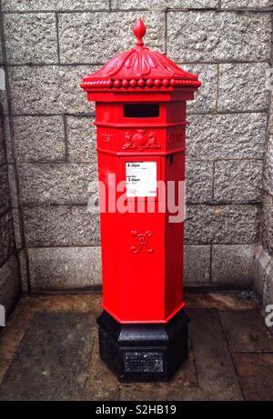 A red Victorian hexagonal Penfold pillar box near Tower Bridge in London, England - Stock Photo