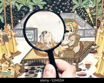 Looking through the Magnifying glass at the Indian miniature painting in the museum - Stock Photo