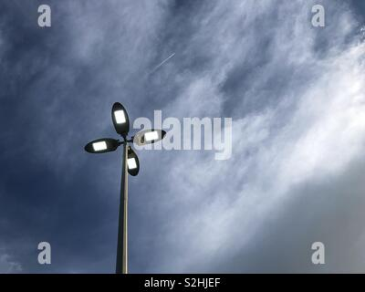 Street lamp against stormy sky and airplane chem trails. - Stock Photo