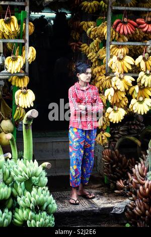 Woman standing in the entrance of her banana shop in Yangon, Myanmar - Stock Photo