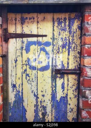 Old flaking paint on an outside toilet door. - Stock Photo