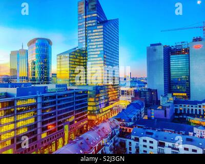 A full spectrum of colors during sunrise shown in the sky and the reflection of the sky in the glass of the business offices of the financial district of the city - Stock Photo