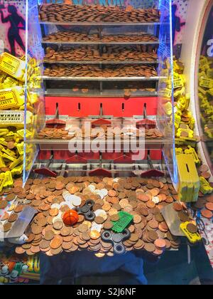Penny falls machine in a seaside amusement arcade. - Stock Photo