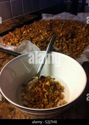 Home made granola and yoghurt in a bowl. In the background is the freshly made granola on a baking tray - Stock Photo