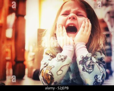 Young girl crying and screaming in the floor - Stock Photo