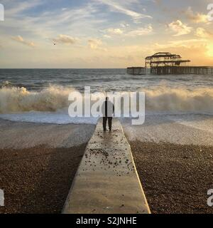 Man standing on jetty as big wave crashes against the shore - the skeleton of burnt down Brighton pier at the horizon - Stock Photo