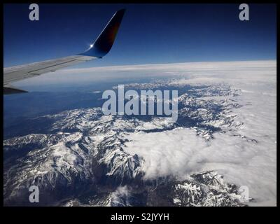 A view above the clouds of The Pyrenees from seat 26F on a Jet2 aircraft en route from Leeds Bradford Airport (UK) to Barcelona El Prat, Spain. - Stock Photo