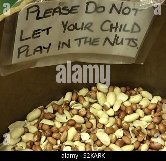 Hand written sign in a grocery shop displayed on an open container of nuts - Stock Photo