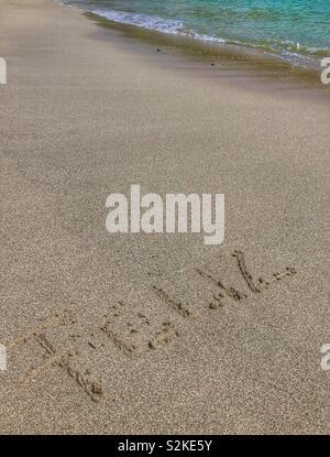 Feliz written in the sand. - Stock Photo