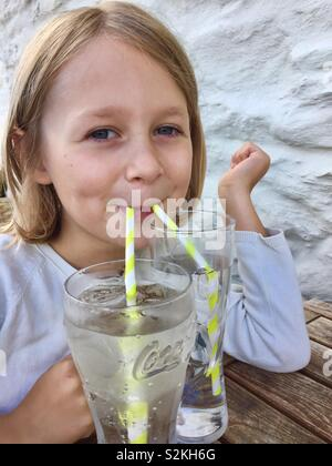 Female child drinking out of two glasses with two straws - Stock Photo