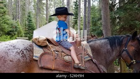 Young boy wearing cowboy hat sitting atop grandpa's horse at mountain camp - Stock Photo