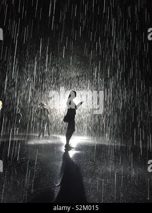 Woman standing in rain room - Stock Photo