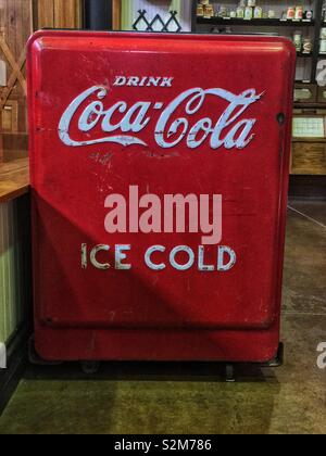 Antique red coke cooler with drink coca-cola and ice cold written on it. - Stock Photo