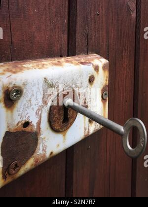 Key in a rusty old door lock - Stock Photo