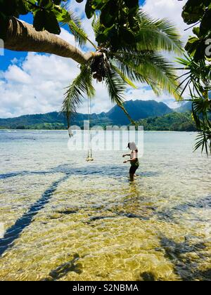 A tourist trying to get to the swing hanging on the coconut tree on a secret Beach in North Shore Kauai. - Stock Photo