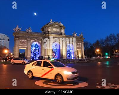 Taxi and Alcalá gate, night view. Madrid, Spain. - Stock Photo