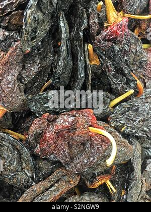 Full frame of dried whole ancho poblano Chile peppers for sale as fresh produce. - Stock Photo