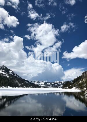 Echo Lake high in the Sierras of California still partially frozen,with snow, at the end of May 2019. - Stock Photo