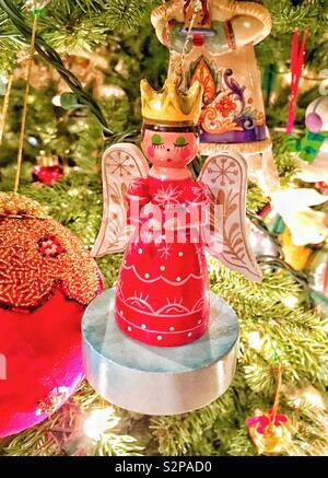 Wooden Angel ornament in red dress wearing gold crown praying on Christmas tree surrounded by other ornaments and pine needles - Stock Photo