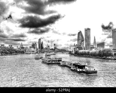 A view from Waterloo Bridge looking along the River Thames towards the City of London, England on an overcast day. - Stock Photo