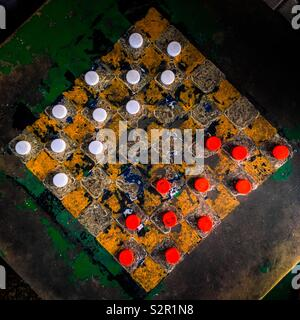 Plastic bottle caps (checkers pieces) are seen positioned before the game begins on an outdoor checkerboard table in the park in San Salvador, El Salvador, 26 November 2018. - Stock Photo