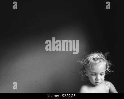 Black and white portrait of curly-haired toddler looking down with negative space. - Stock Photo
