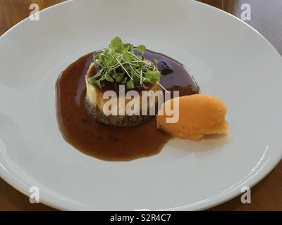 A traditional timbal of haggis and tatties (mashed potatoes), topped with watercress and with neeps (mashed rutabagas) on the side, is shown plated in a Scottish restaurant. - Stock Photo