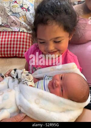 Big sister holding her newborn baby brother - Stock Photo