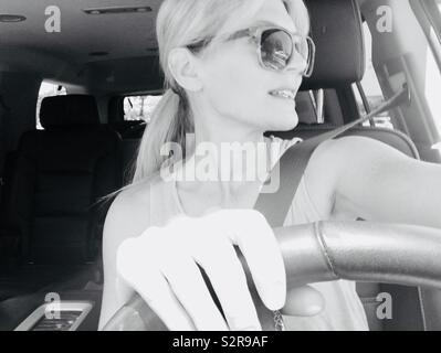 Monochrome , black and white photo of a woman wearing sunglasses and hair in a ponytail, driving the car ready for a road trip adventure - Stock Photo