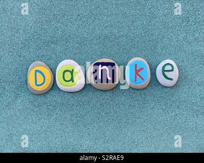 Danke, thank you in german language composed with colored stones over green sand - Stock Photo