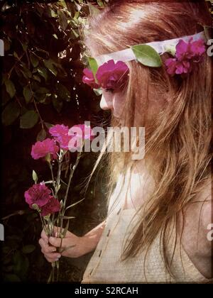 A beautiful girl with long brown, blonde hair wearing a crown of ivy leaves and pink carnations holding flowers on a summers afternoon - Stock Photo