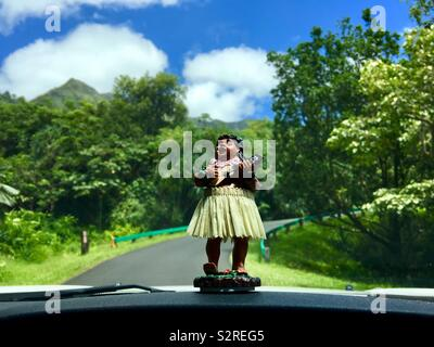 Hula bobblehead in a grass skirt on a car dashboard playing the ukulele while driving in Hawaii - Stock Photo