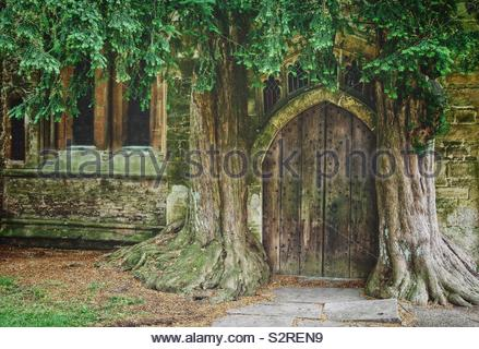Old church door flanked by two ancient Yew trees, St Edwards church Stow On The Wold, UK; said to be the inspiration for Tolkien's Moria door. - Stock Photo