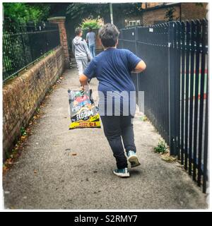Obese child with crisps trying to run and keep up - Stock Photo