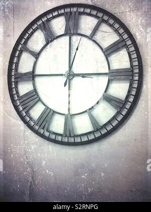 A black and white photo of a large clock on the wall - Stock Photo