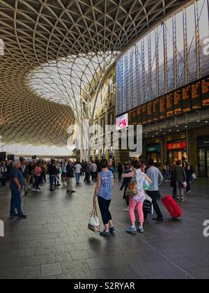 Passengers people waiting in he concourse at London King's Kings Cross railway station mainline, watching the display train timetable. - Stock Photo