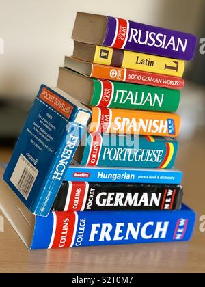 A stack of English to other language dictionaries. - Stock Photo